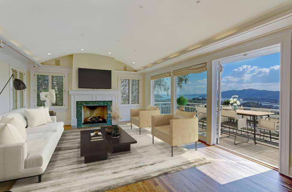 The living room features a fireplace and glass walls that open to deck overlooking the Bay.