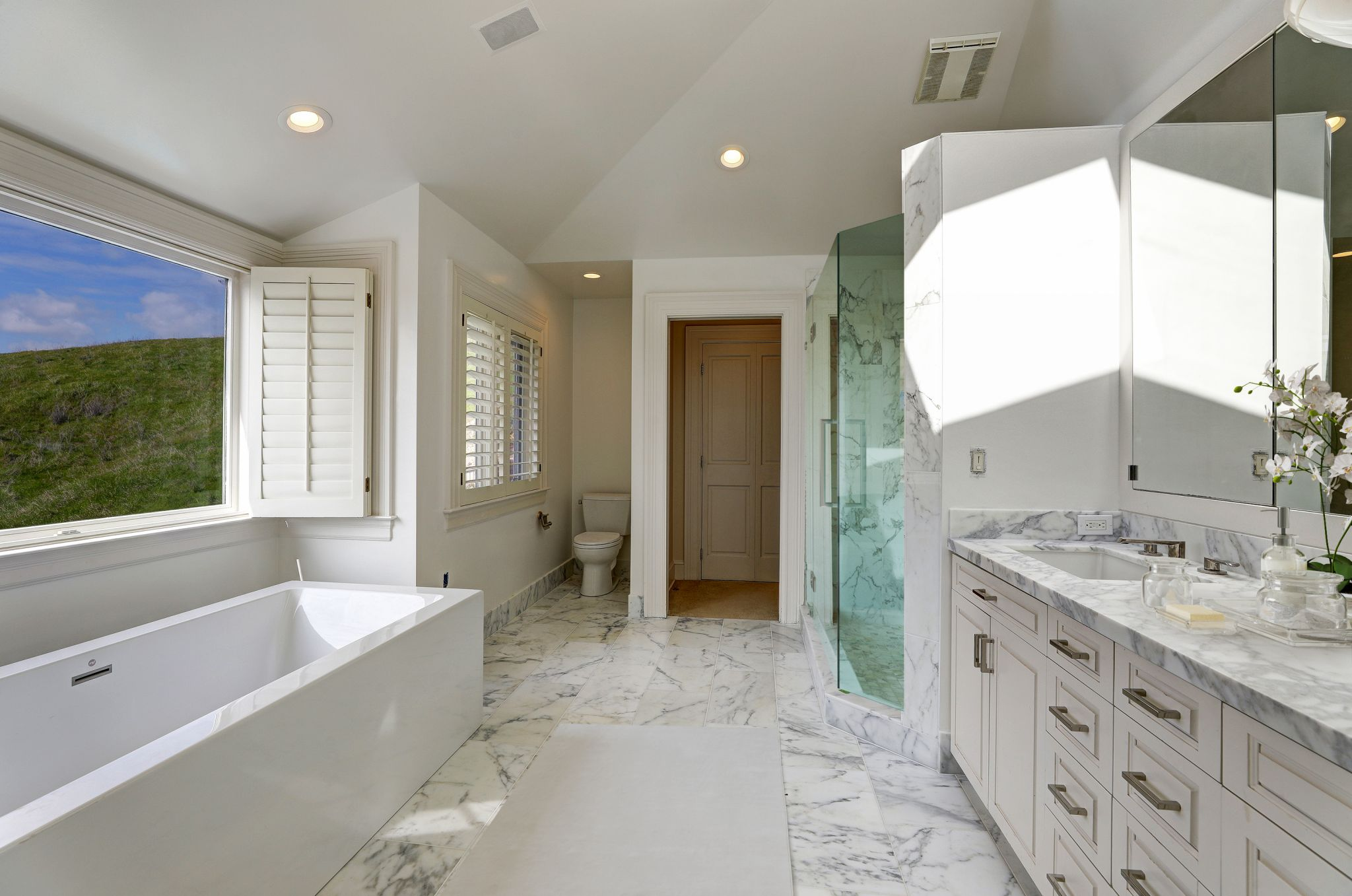 In the master bath there are marble finishes, radiant floors, plus both a shower and tub, complete with a view of Mt. Tam.