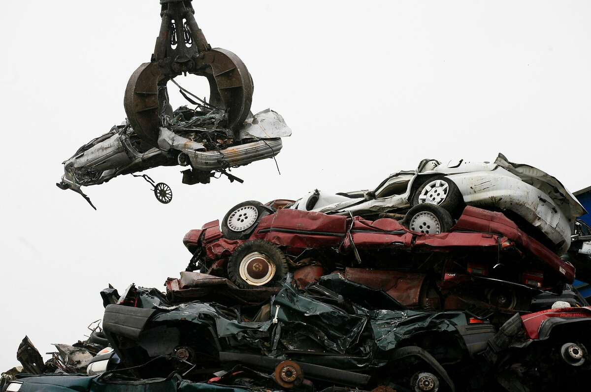 """A crane lifts a flattened car from a stack of similar vehicles to a shredder at Gershow Recycling Corp. in Medford, N.Y., Thursday, Aug. 6, 2009. Many of the scrapped vehicles are part of the """"cash for clunkers"""" program. The Senate is poised to pump $2 billion more into the popular """"cash-for-clunkers"""" program after agreeing to give shoppers until Labor Day to make a deal on more energy-efficient models. (AP Photo/Mark Lennihan)"""