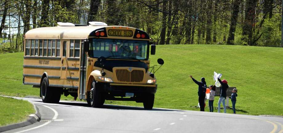 Parents and students wave to a school bus taking part in the Bethel Teacher Appreciation Day parade on Tuesday. About 180 staff members were expected to participate. April 5, 2020, in Bethel, Conn. Photo: H John Voorhees III / Hearst Connecticut Media / The News-Times