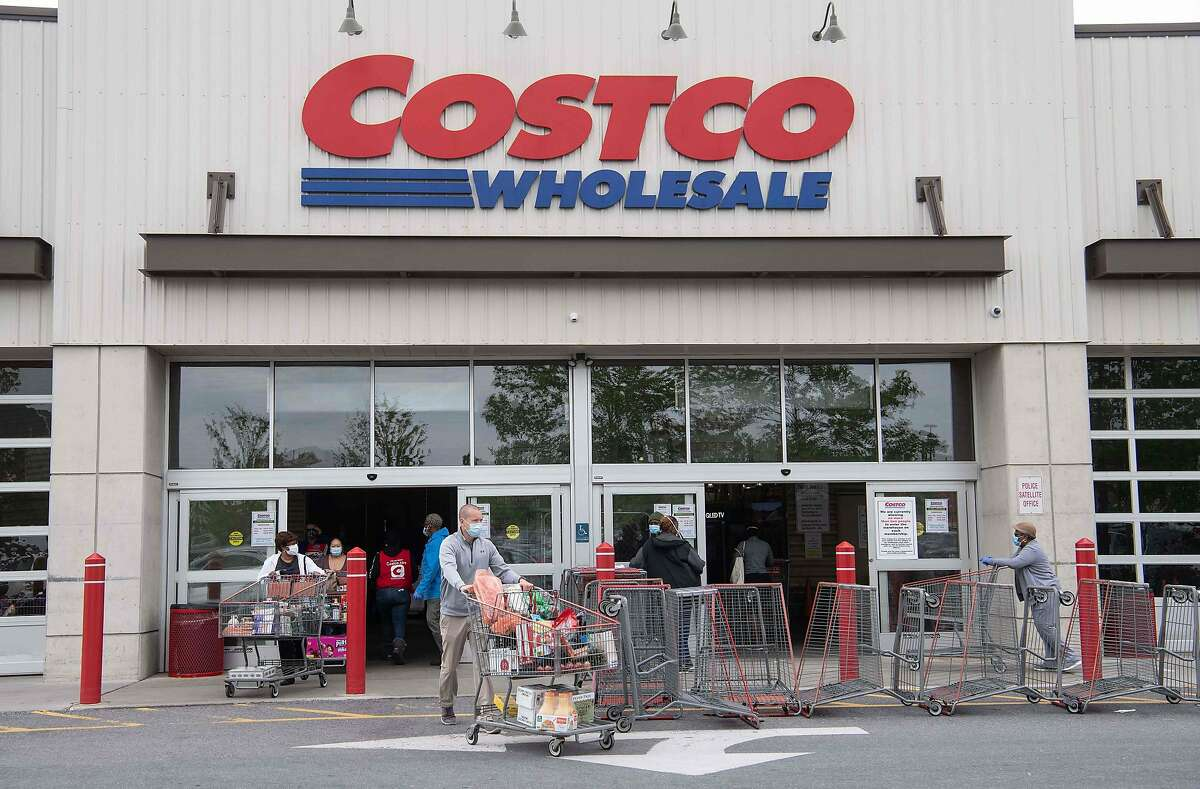 Shoppers walk out with full carts from a Costco store in Washington, DC, last May. A few Costco pharmacies in California are now offering the coronavirus vaccine.