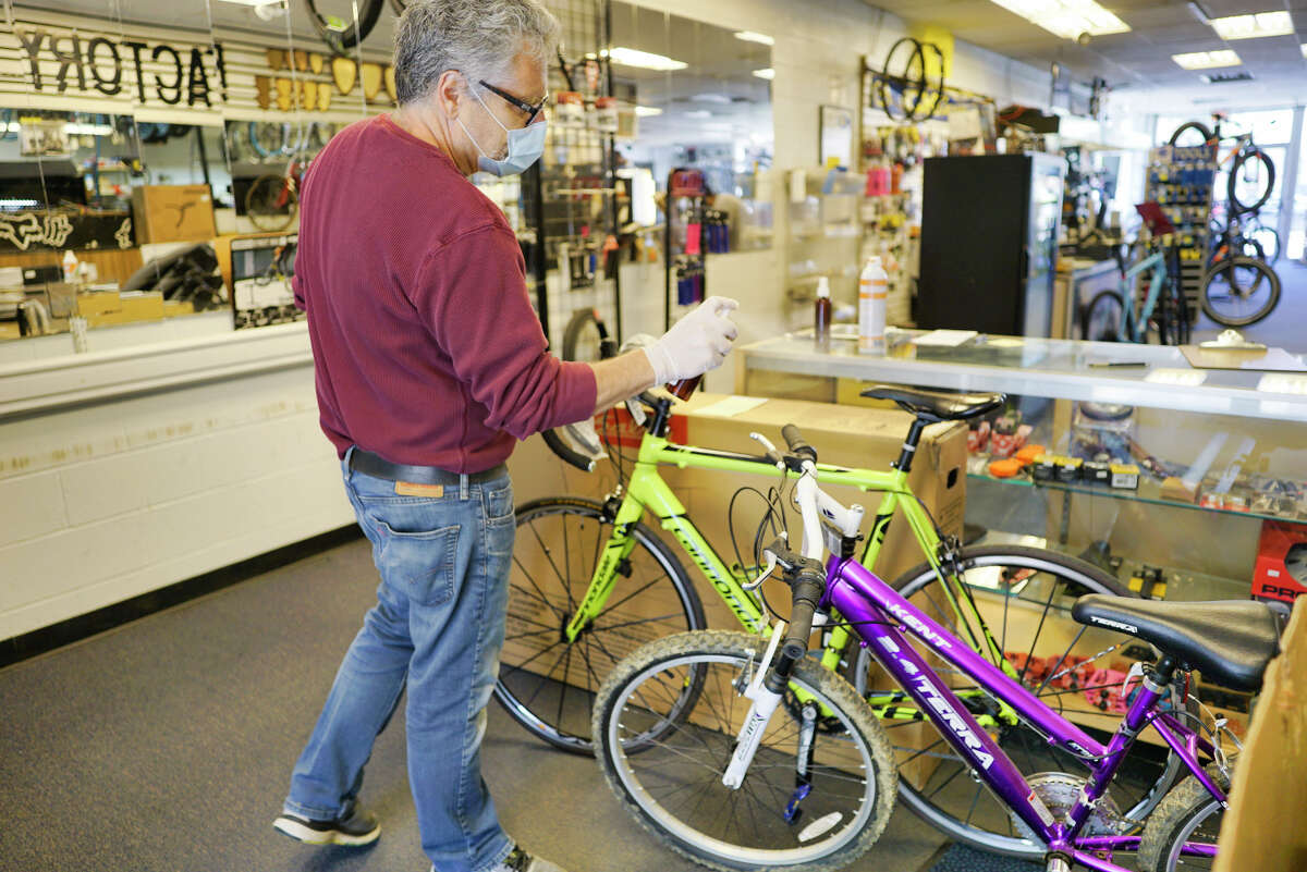 Jeff Pepper, owner of CK Cycles, sprays a disinfectant on bikes brought in for repairs at his shop on Tuesday, May 5, 2020, in Colonie, N.Y. Customers are met in the parking lot by employees of the bike shop. (Paul Buckowski/Times Union)