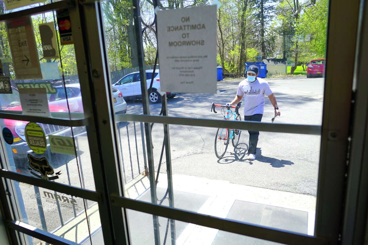 Rojay Ragbeer, an employee of CK Cycles, wheels in a customer's bicycle that was dropped off for repairs in the parking lot of the bike shop on Tuesday, May 5, 2020, in Colonie, N.Y. (Paul Buckowski/Times Union)