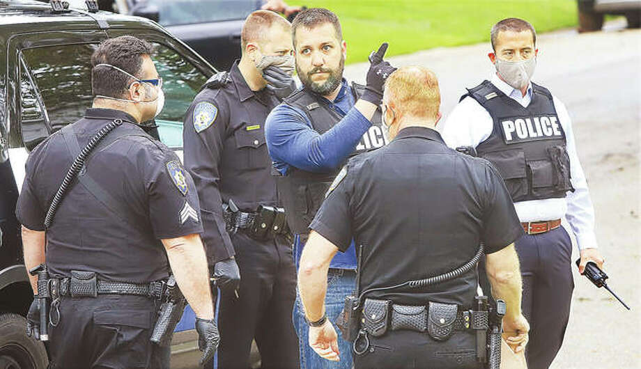 Alton Police detective P.J. Bennett, center, holds a loaded gun magazine removed from a gun which was confiscated in the back yard where the suspect was shot. Bennett who was one of the first officers on the scene, talks to other officers about what happened.