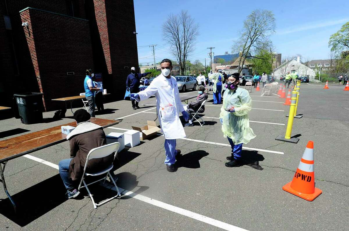 Medical personnel of DOCS Urgent Care Stamford administer a COVID-19 nasal swab tests to residents of Stamford's Westside at a walk up testing site for the Coronavirus at AME Bethel Church in Stamford, Connecticut on May 2, 2020.