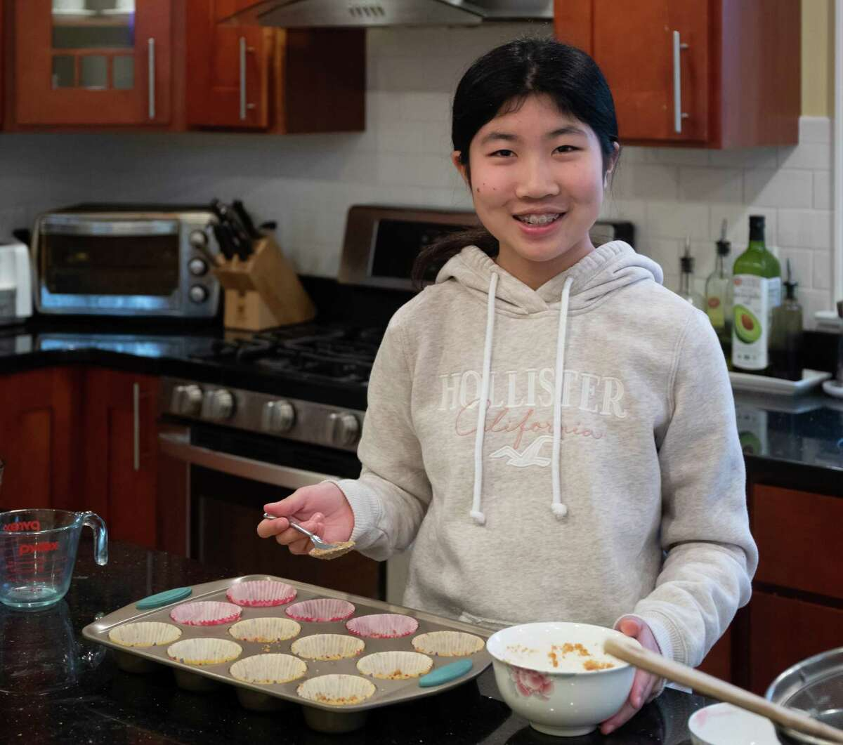 Annabelle Zheng, a seventh grader at Middlebrook School, bakes mini raspberry cheesecakes at home in Wilton, Ct. May 2020