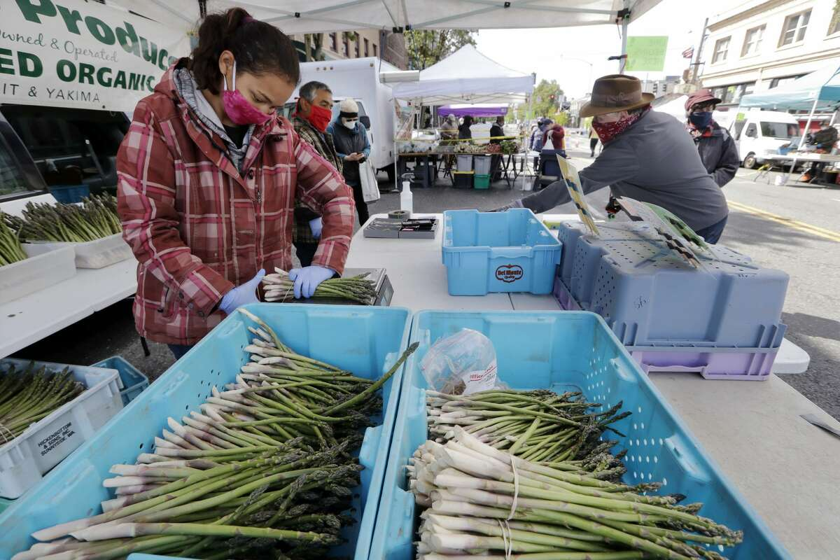 In this AP Photo, Farmer Alegria Canales stacks asparagus as a customer behind completes his purchase at her family's stand in the West Seattle Farmers Market during its first opening in nearly two months because of the coronavirus outbreak Sunday, May 3, 2020, in Seattle. Wearing masks while shopping could become a reality for those visiting the Big Rapids Farmers Market this year.