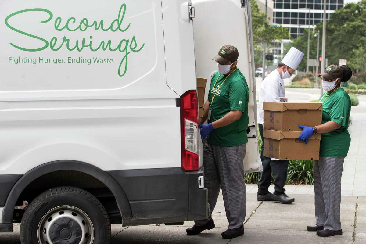 Gerardo Cordoba, left, and Cindy Bankhead help load a refrigerated van with prepared frozen meals for Second Servings on Wednesday, April 8, 2020 in Houston. Second Servings, Houston's food rescue non-profit, is teaming with Hess Corporation and Sysco to create Dinner On Us, a program of chef-prepared take-home family meals for furloughed and unemployed hospitality workers in Houston. Beginning April 9, Second Servings will distribute 10,000 meals a week prepared at Hess offices in downtown Houston and distributed Tuesdays and Thursday downtown at Avenida de las Americas. the freshly prepared and frozen family meals serve 7-8 people.