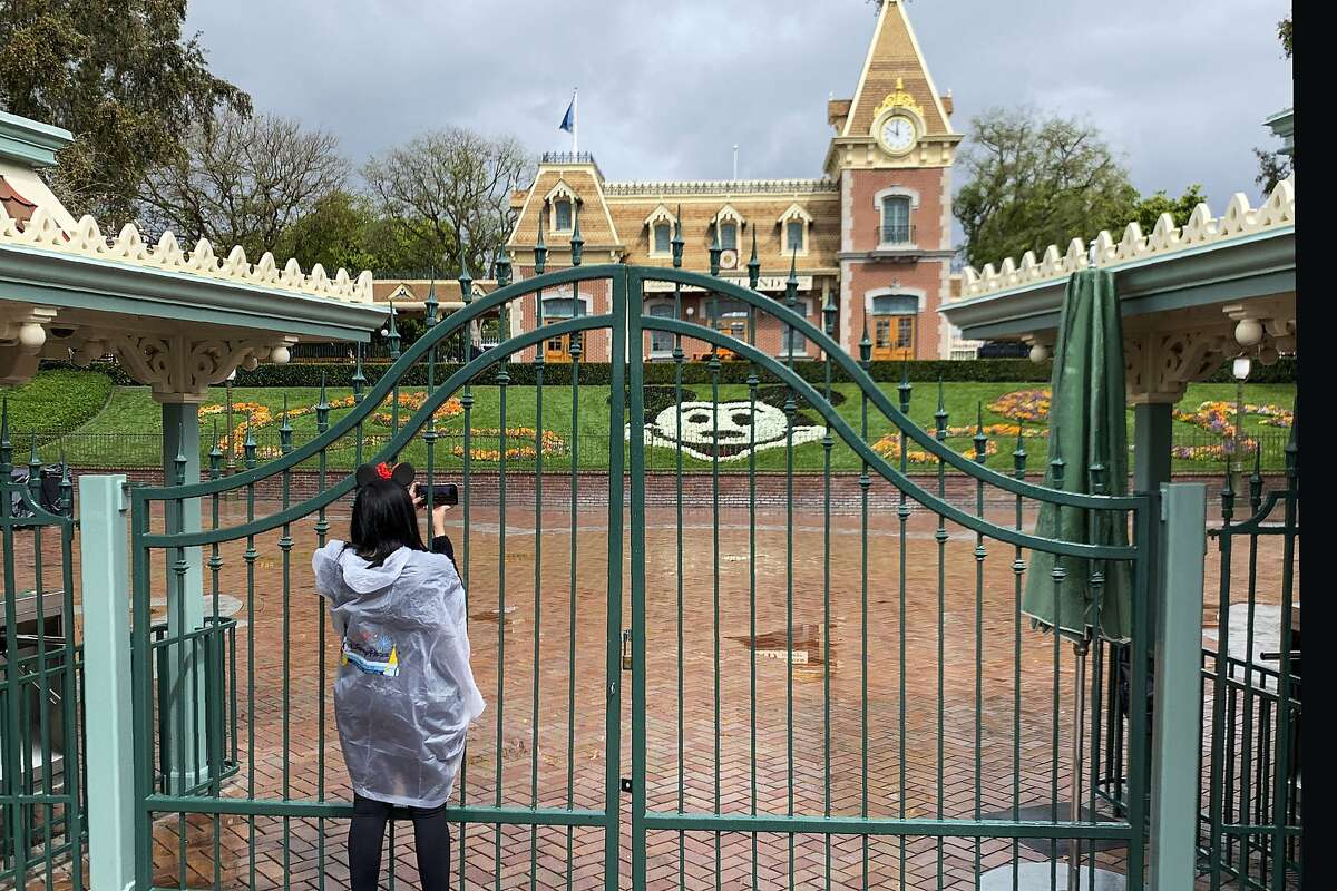 FILE - In this March 16, 2020, file photo, a visitor to Disneyland in Anaheim, Calif., takes a photo through a locked gate at the entrance. Disneyland has been shut down due to the novel coronavirus outbreak. If Gov. Gavin Newsom's so-called roadmap to ease coronavirus restrictions hinted at a return to a normal Californians could appreciate - a summer trip in the car - it quickly became apparent they wouldn't be leaving home soon. The governor's sobering message foreshadows a summer without baseball games under the lights, large outdoor concerts, rides at amusement parks or trips to the beach. (Jeff Gritchen/The Orange County Register via AP, File)
