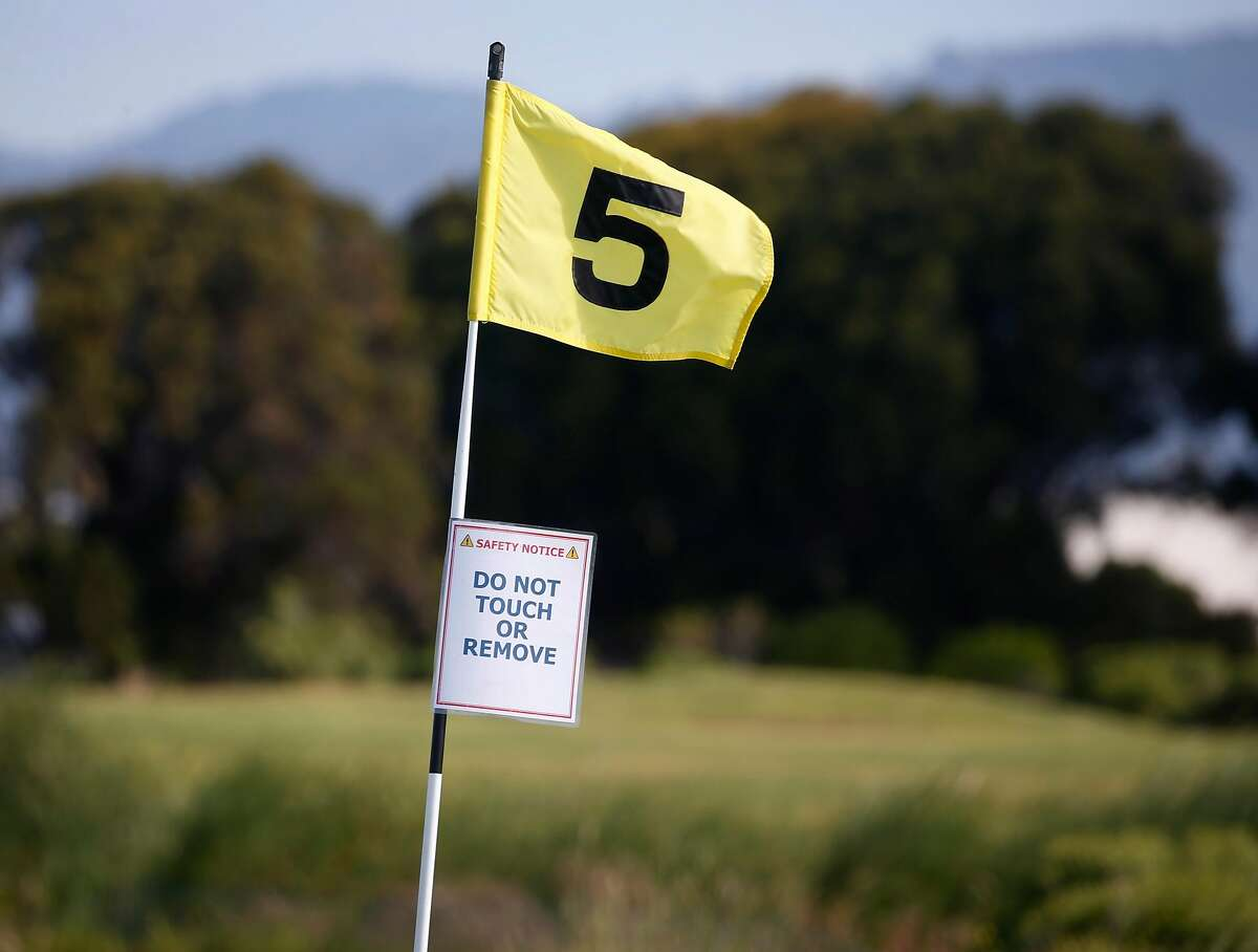 Flagsticks remain in the hole at all times at Metropolitan Golf Links in Oakland, Calif. on Tuesday, May 5, 2020. Some outdoor activities such as golf and skateboard parks have been allowed to reopen during the coronavirus pandemic following social distance protocols.