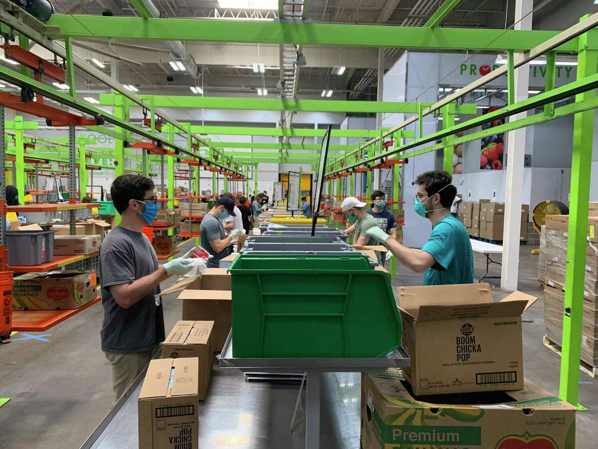 Volunteers pack boxes at the Houston Food Bank.