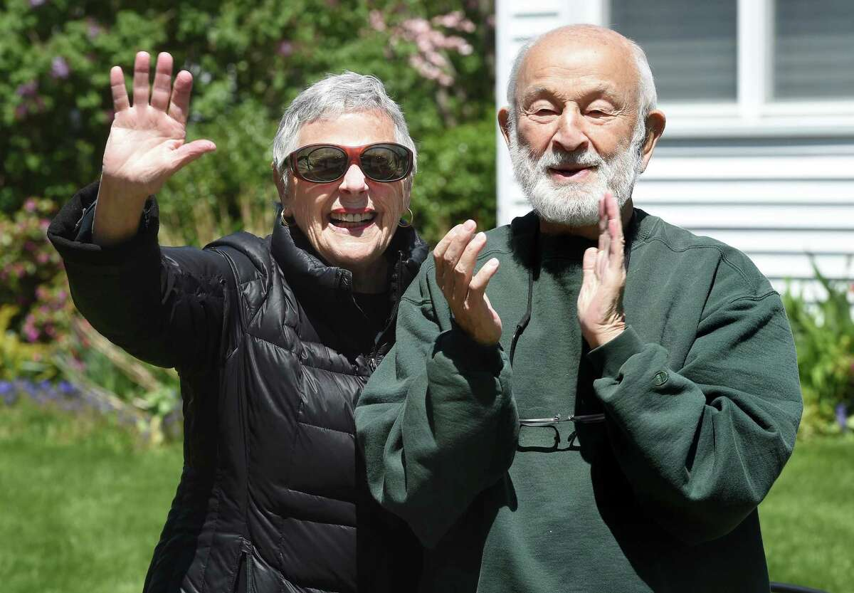 Dick Jacobs, right, and his wife, Cary, stand on the front walkway of their home in New Haven and watch as a parade of cars pass by with happy birthday signs honking their horns for his 90th birthday on May 5, 2020.