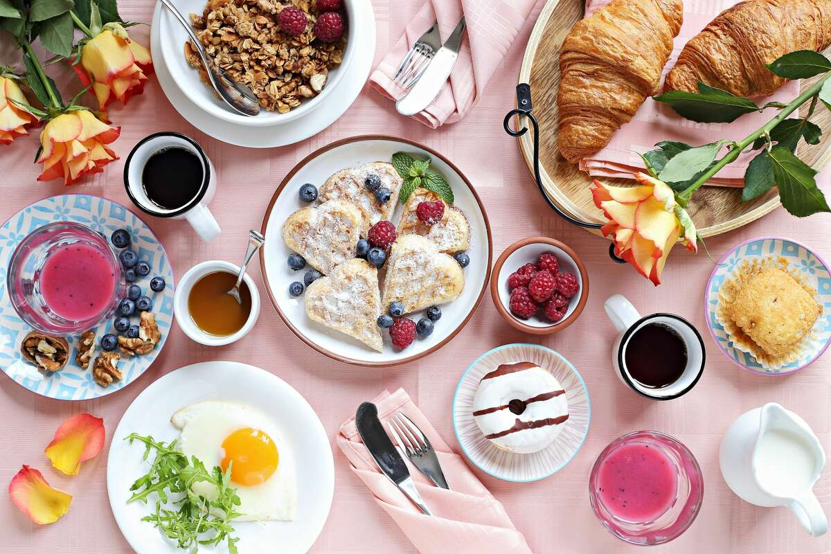 Festive brunch or breakfast set for Valentines day, Mothers day or Easter. Pink background. Overhead view .