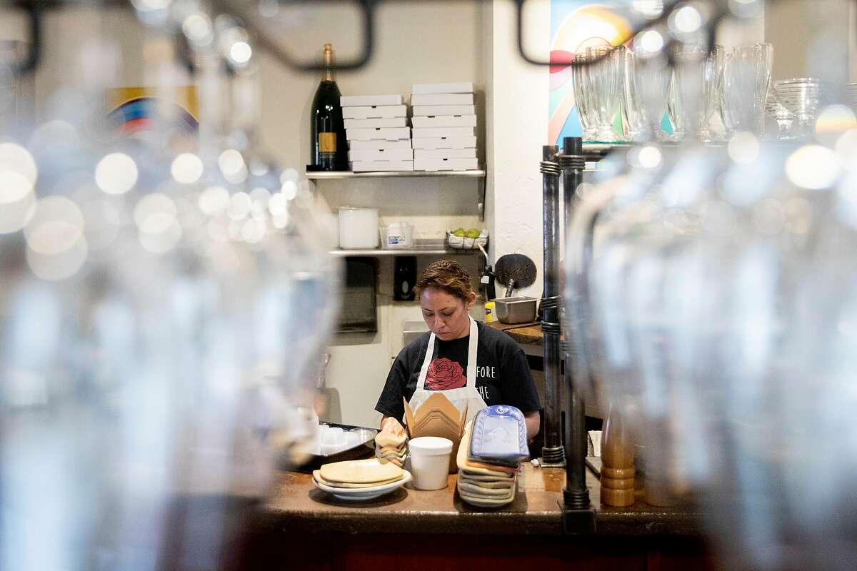 Mirna Fernandez is seen through a row of glassware as she prepares pizza dough fat Fume Bistro in Napa, Calif. Tuesday, May 5, 2020. A handful of businesses in Napa have made the decision to begin reopening their dining rooms at a limited scale ahead of shelter-in-place orders.