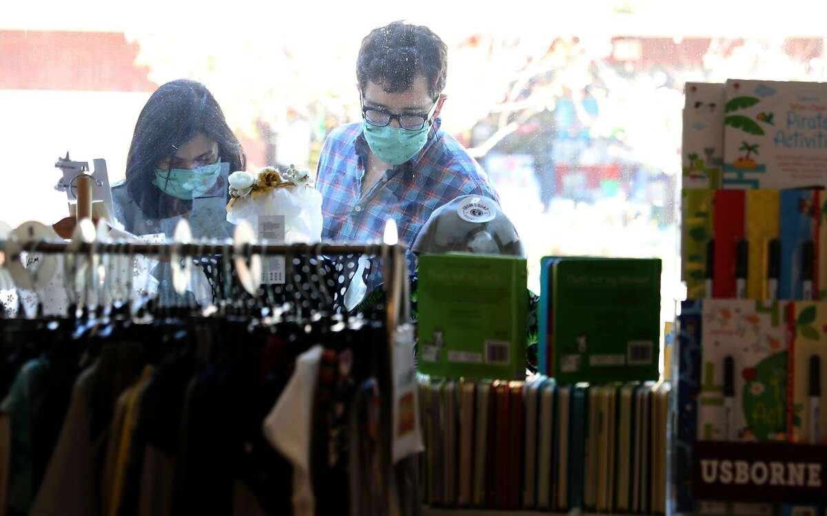 Customers look through the store window of Small Frys, a children's store in Noe Valley which has been open for 36 years seen on Tuesday, May 5, 2020, in San Francisco, Calif.