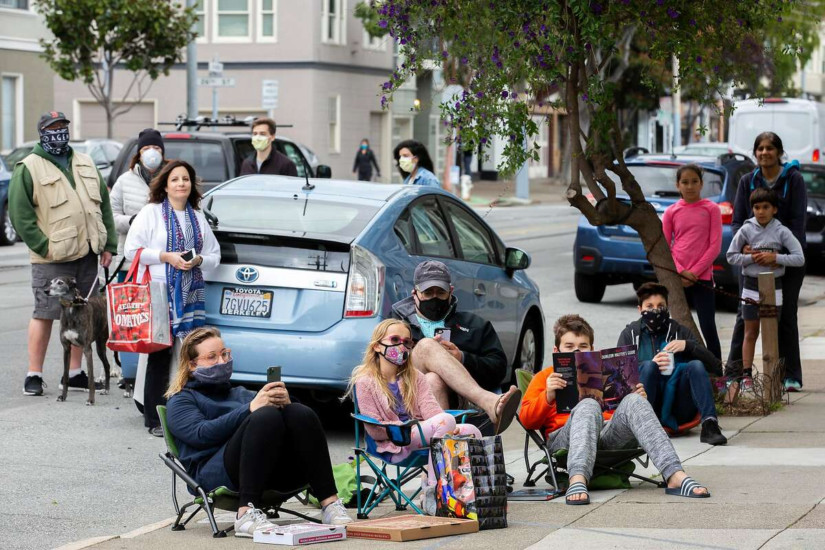 Friends, neighbors and people passing by stop to watch Rachel Garlin sing and play her guitar from her garage to the Noe Valley neighborhood on Friday, April 17, 2020, in San Francisco, Calif.