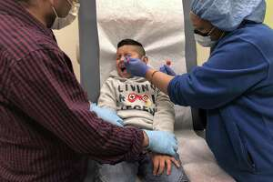 Guatemalan immigrant Junior, 7, receives a COVID-19 swab test from a nurse as his father Marvin holds him down at a clinic on May 5, 2020 in Stamford, Connecticut. Junior and Marvin were being re-tested to see if they are now are negative, a month after getting sick from coronavirus.