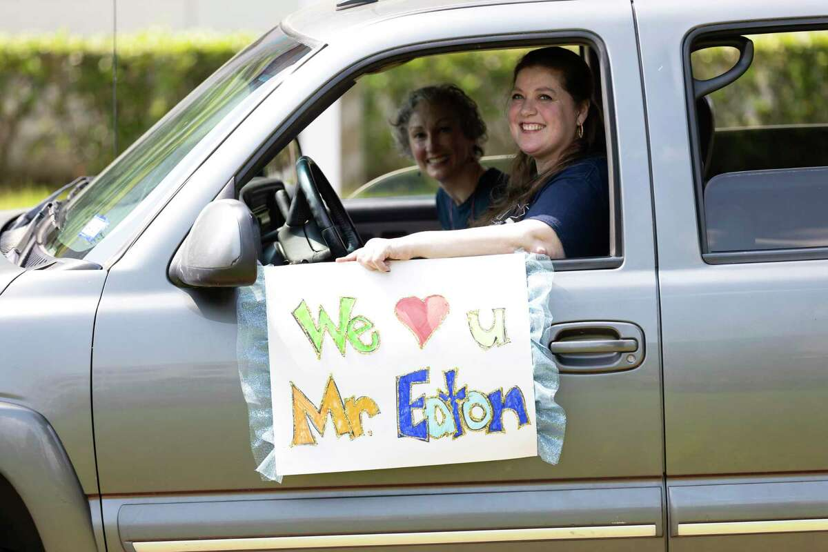 Community members of Montgomery County hold signs during a drive-by car parade at TIRR Memorial Hermann The Woodlands Medical Center, Tuesday, May 5, 2020. An estimated 70 vehicles took part in the celebration of Lake Creek High School Principal Phil Eaton's recovery from battling the novel coronavirus.