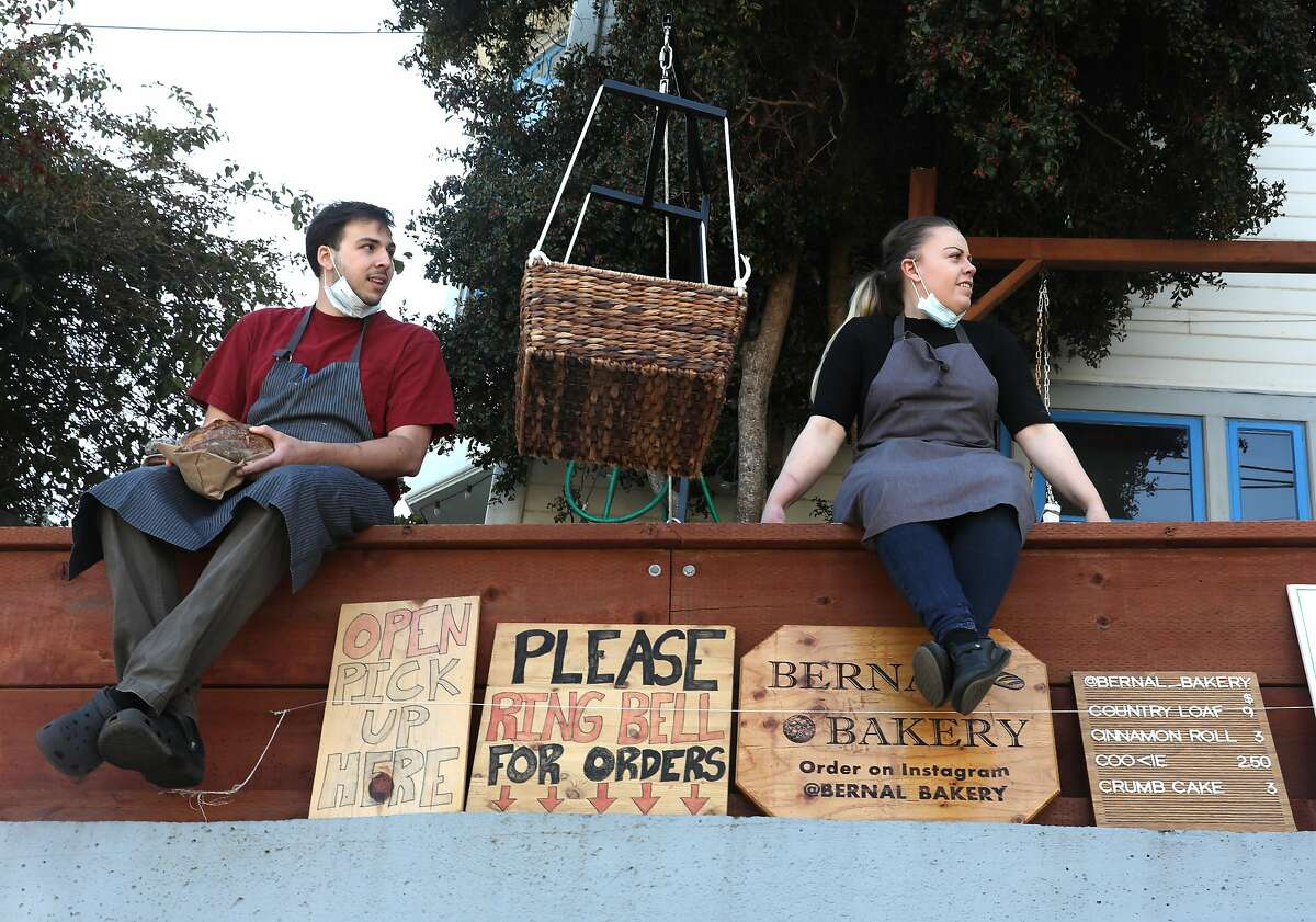 Chefs Ryan Stagg (left) next to his fiancee Danielle Banchero (right) as they wait for a customer at their pop-up bakery out of their home on Tuesday, May 5, 2020, in San Francisco, Calif.