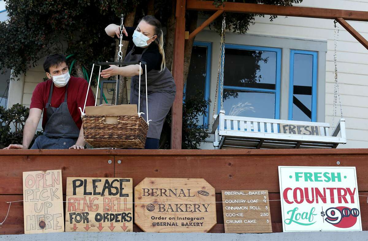 Chefs Ryan Stagg (left) next to his fiancee Danielle Banchero (right) as they load cinnamon rolls for a customer seen at his pop-up bakery out of their home on Tuesday, May 5, 2020, in San Francisco, Calif.