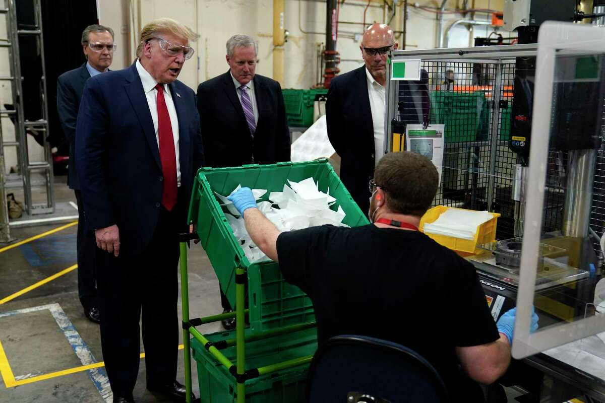 President Donald Trump participates in a tour of a Honeywell International plant that manufactures personal protective equipment, Tuesday, May 5, 2020, in Phoenix, with Tony Stallings, vice president of Integrated Supply Chain at Honeywell, right and White House chief of staff Mark Meadows.