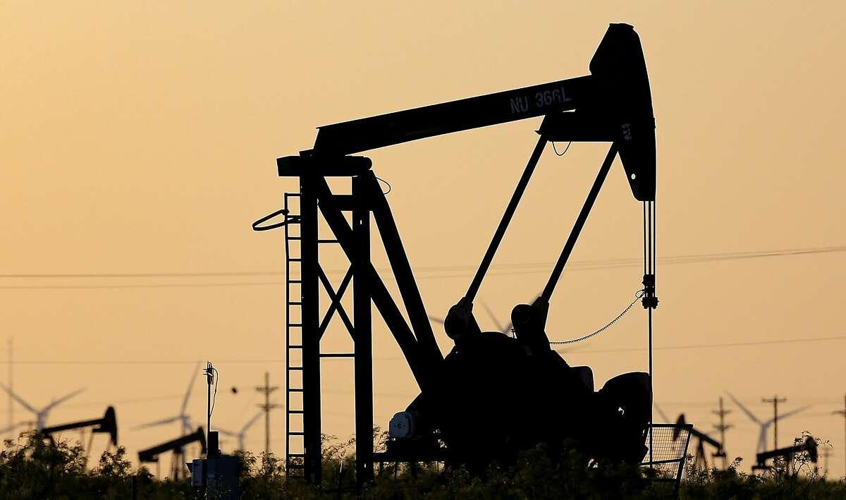 Oil pumpjacks and windmills outside of Kermit,Texas on Sunday, April 26, 2020.