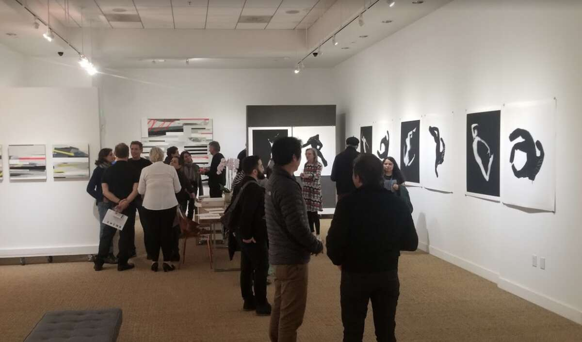 FILE - Guests mingle inside Art Ventures Gallery in March. The gallery reopened Saturday and plans to open again Wednesday in spite of the modified shelter-in-place order, which does not define art galleries as essential businesses.