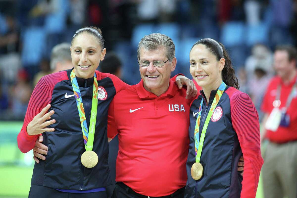 UConn alums Diana Taurasi and Sue Bird pose celebrate after coach Geno Auriemma after winning their fourth career gold medal at the 2016 Olympics in Brazil.
