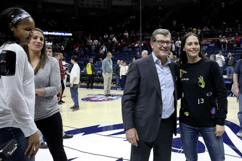 Former UCoonn players Caroline Doty and Maya Moore watch coach Geno Auriemma with Sue Bird after the Huskies defeated South Carolina in February 2017 for their 100th consecutive win.