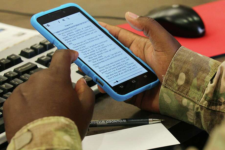 "U.S. Army Captain Noah Washington, 40, of Jackson, Mississippi opens his first book from the Bexar BiblioTech at the Warrior and Family Support Center in Joint Base San Antonio-Fort Sam Houston, Monday, July 14, 2014. The digital library will make available its content to military personnel and families of personnel under going treatment and recovery at Brooke Army Medical Center. Washington downloaded John Grisham's, ""The Runaway Jury"". Photo: JERRY LARA, Staff / San Antonio Express-News / © 2014 San Antonio Express-News"