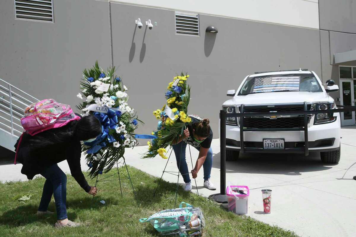 Bexar County Detention Center employees secure wreaths toppled by winds at a temporary memorial for Bexar County Sheriff's Deputy Timothy De La Fuente, 53, at the Bexar County Detention Center on May 1, 2020. The 27-year veteran died on Thursday after he was diagnosed with COVID-19.