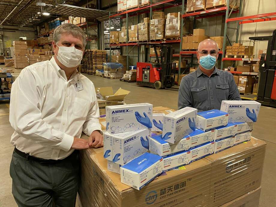 Ed Ness, CEO of Munson Healthcare, and Dodd Russell, CEO of Skilled Manufacturing Incorporated with personal protection equipment procured by Russell. (Courtesy Photo)