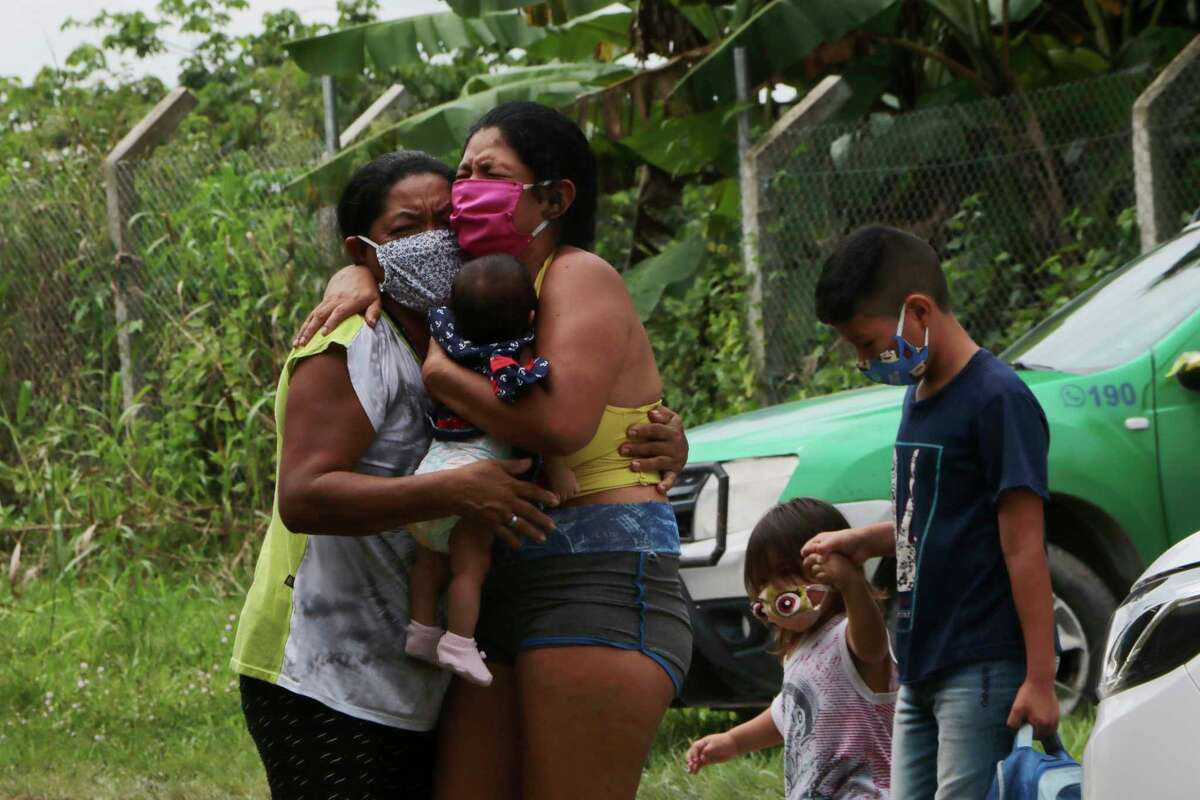 Relatives mourn at the roadside while waiting for funerary service workers to pick up of the body of Arlen Laranjeira Bezerra, 39, a victim of the new coronavirus who died after fleeing the emergency room of the Delphina Rinaldi Abdel Aziz Hospital in Manaus, Amazonas state, Brazil, Tuesday, May 5, 2020. Bezerra was admitted to undergo treatment for COVID-19 disease and after escaping from the hospital at dawn, his body was found by family members approximately 200 meters from it.