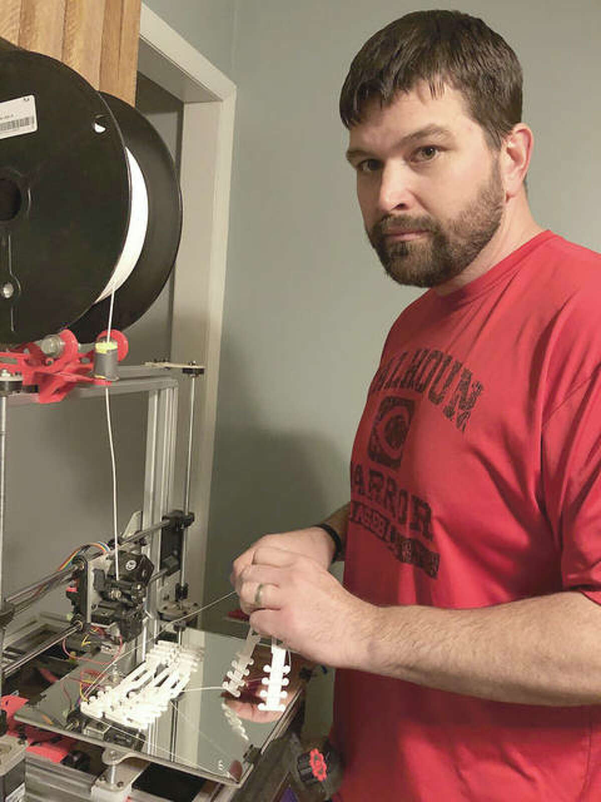 Calhoun High School industrial technology teacher Seth Grimes has used the school's 3-D printer to create face mask holders. His wife, Stacey, who works at Jerseyville Community Hospital, suggested the project after seeing posts about such devices on Facebook.