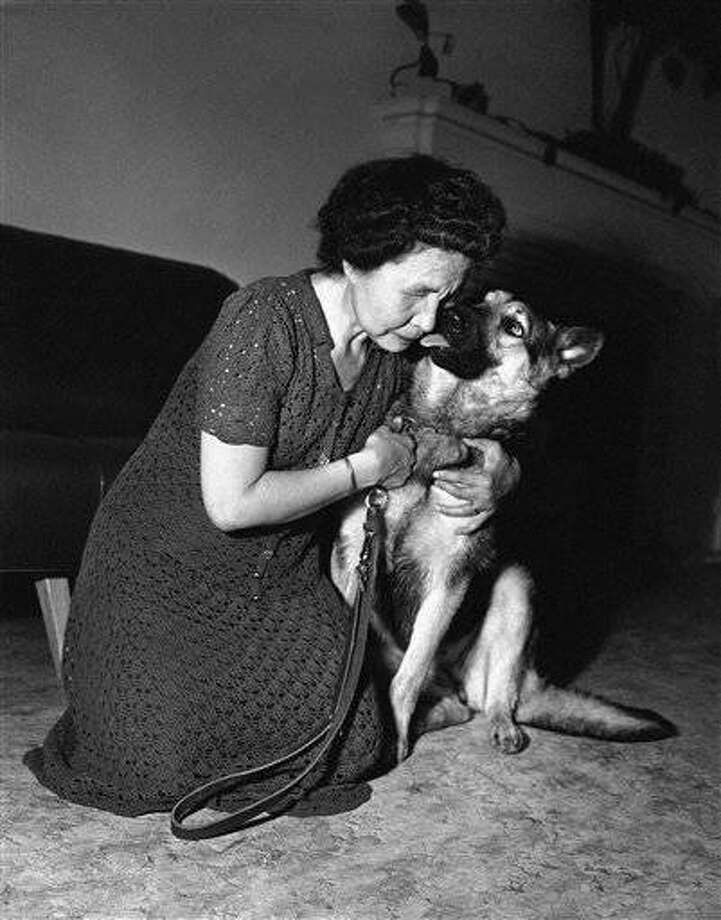 Melba King of Seattle, Wash., who is blind, gets an affectionate kiss from her new guide dog after a training session at the Guide Dogs for the Blind at San Francisco, Calif. May 6, 1952. The tiny Eskimo woman, blind since birth, lost her former guide dog after it was hit by an auto in Seattle. The new seeing eye dog was provided through the generosity of Seattle residents. (AP Photo/Ernest K. Bennett)