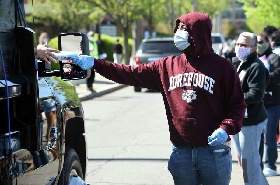 Morehouse College sophomore Jason Gill of New Haven was among volunteers handing out packages of free surgical masks on Winchester Avenue in New Haven's Science Park on May 5, 2020. Photo: Arnold Gold / Hearst Connecticut Media / New Haven Register
