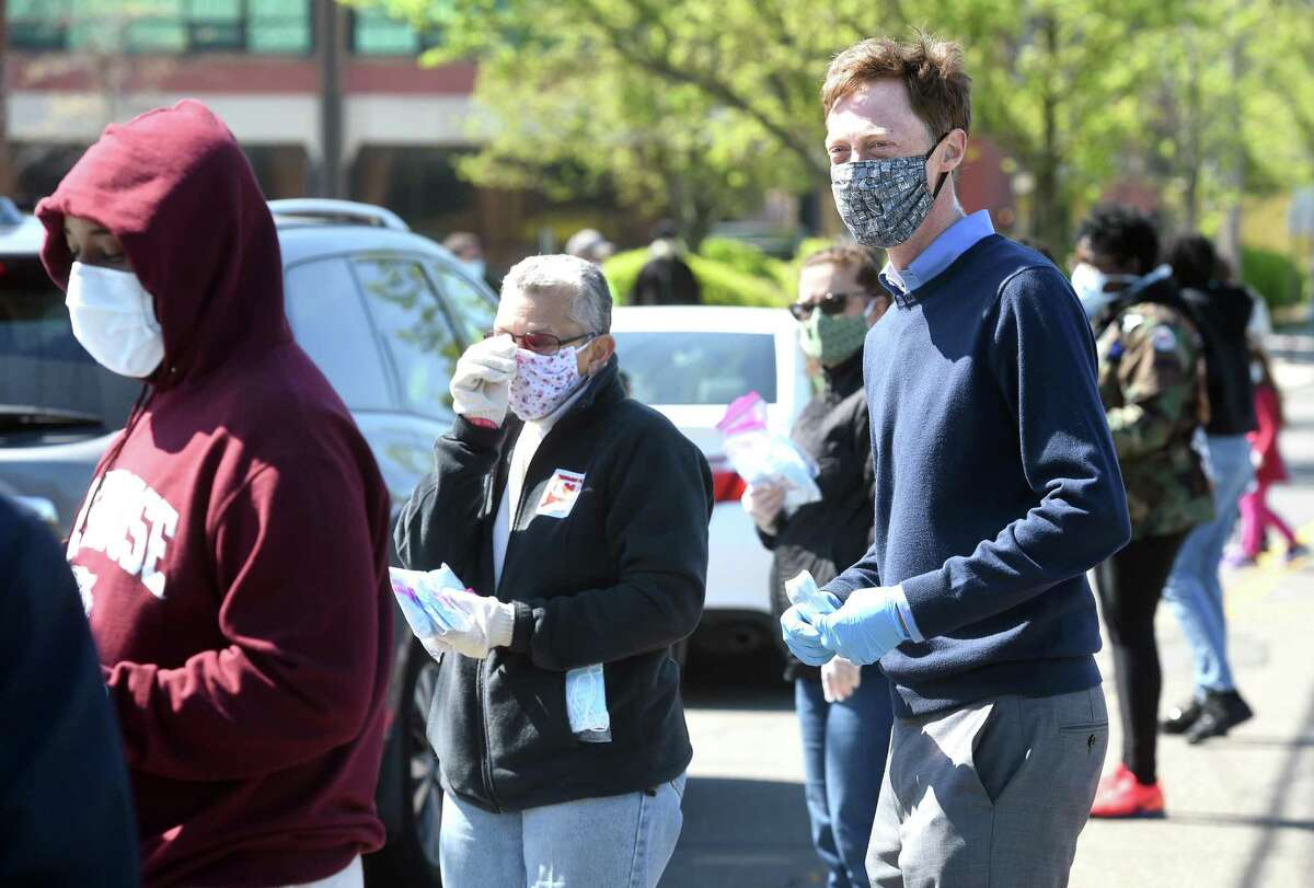 New Haven Mayor Justin Elicker (right) joined volunteers handing out packages of free surgical masks on Winchester Avenue in New Haven's Science Park on May 5, 2020.