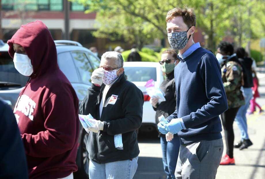 New Haven Mayor Justin Elicker (right) joined volunteers handing out packages of free surgical masks on Winchester Avenue in New Haven's Science Park on May 5, 2020. Photo: Arnold Gold / Hearst Connecticut Media / New Haven Register