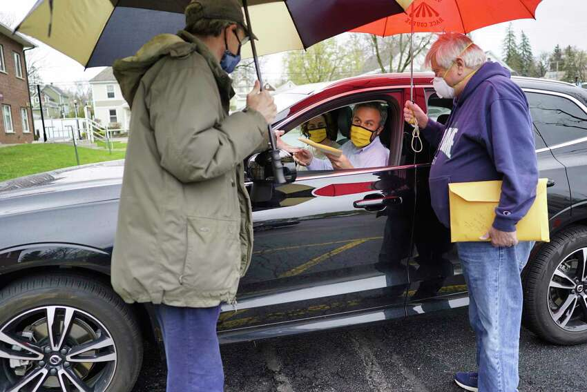 1st Bank of Scotia lawyer, William Bates, foreground left, and attorney Gary O'Connor, foreground right, work with Joshua Poupore and his wife, Patricia Poupore as they sit in their vehicle outside the offices of 1st Bank of Scotia on Monday, April 27, 2020, in Scotia, N.Y. Joshua and Patricia came to the bank to sign papers for the house they are purchasing. (Paul Buckowski/Times Union)