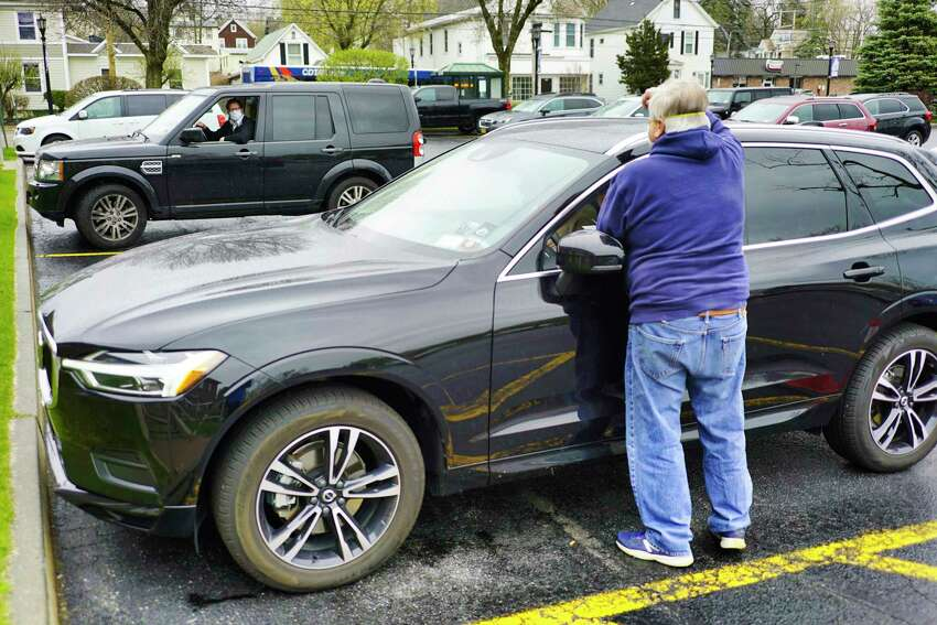 Peter Murray, background, talks with attorney Gary O'Connor as O'Connor stands near the vehicle of his clients outside the offices of 1st Bank of Scotia on Monday, April 27, 2020, in Scotia, N.Y. Joshua Poupore and his wife, Patricia Poupore came to the bank to sign papers for the house they are purchasing. (Paul Buckowski/Times Union)