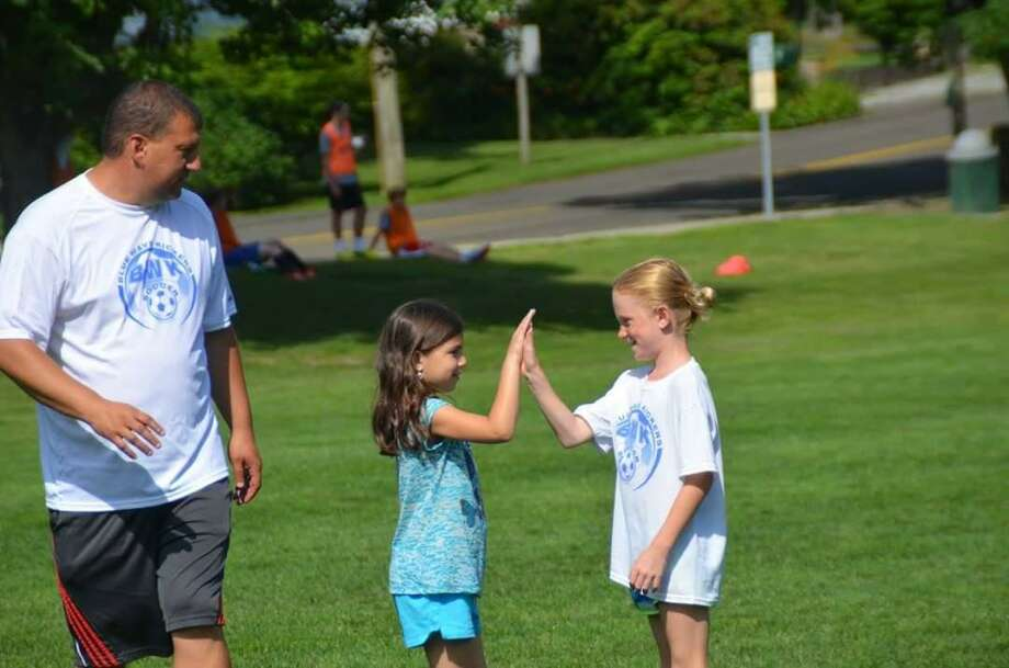 Jon Bradley of the Darien Soccer Association coaching his daughter, Sammi Bradley and Kelly Holmes. He wants to get back to these times. Photo: Contributed /