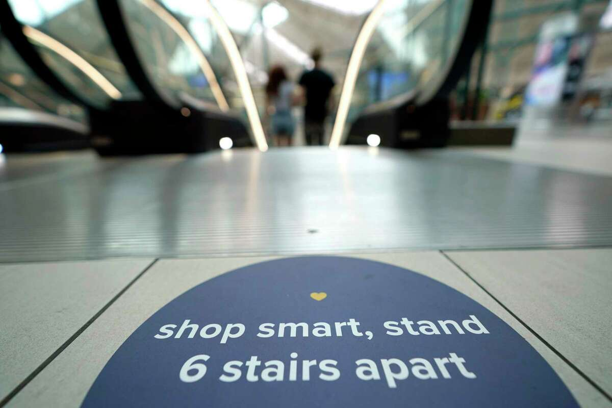 A social distancing sign is posted on the floor near an escalator at The Woodlands Mall Tuesday, May 5, 2020, in The Woodlands, Texas. The mall reopened Tuesday with increased health and safety measures in place.Texas' stay-at-home orders due to the COVID-19 pandemic have expired and Texas Gov. Greg Abbott has eased restrictions on many businesses that have now opened. (AP Photo/David J. Phillip)