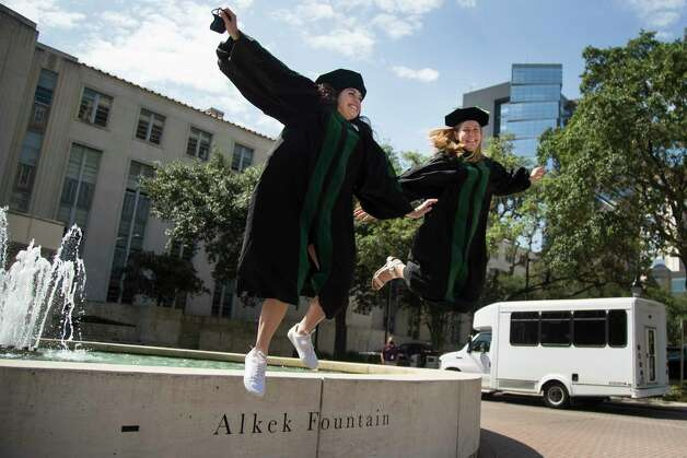 Medical school graduates Dr. Jayme Castillo, left, and Dr. Ashley Mack jump from the Alkek Fountain for a photo as they celebrate after picking up their graduation gowns outside Baylor College of Medicine on Wednesday, May 6, 2020 in Houston. Due to coronavirus restrictions, the medical school will holds a live virtual graduation on May 21, 2020. Photo: Brett Coomer, Staff Photographer / © 2020 Houston Chronicle