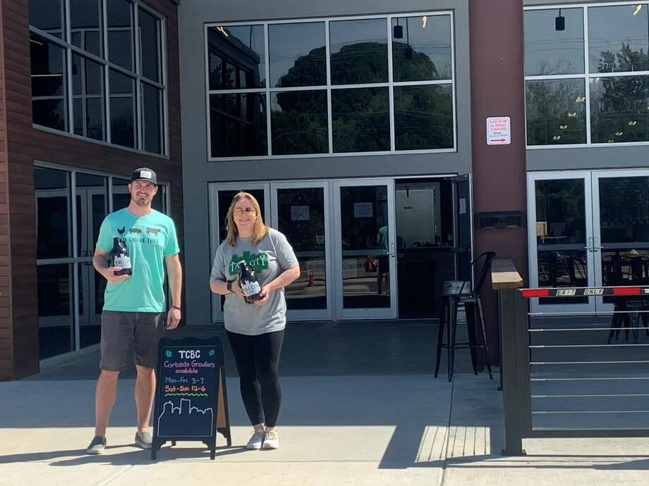Jeff Thomas, left, and Kellyn Heck hold growlers filled with beer as they wait outside the doors of Tall City Brewing Co. to serve customers pulling into the business for curbside service. Thomas, co-owner of Tall City Brewing Co., said the curbside service has been a success with customers looking to get growlers filled with their favorite brews. Photo: Courtesy Photo