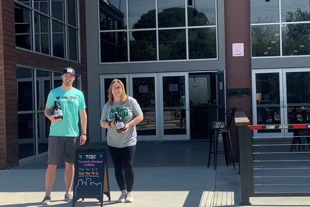 Jeff Thomas, left, and Kellyn Heck hold growlers filled with beer as they wait outside the doors of Tall City Brewing Co. to serve customers pulling into the business for curbside service. Thomas, co-owner of Tall City Brewing Co., said the curbside service has been a success with customers looking to get growlers filled with their favorite brews.