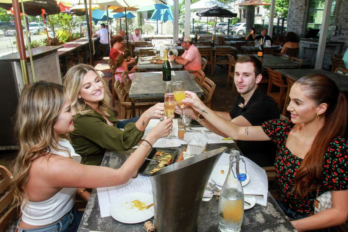 Rocki Tello, from left, Courtney Kennedy, Cody Belvin and Katie Rice toast during lunch at a'Bouzy in Houston as they reopen on May 1, 2020.