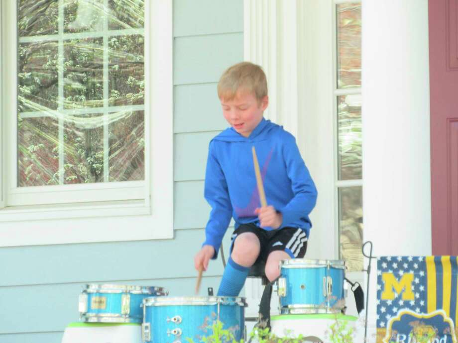 Quintin Rivard, 7, of Midland, plays the drums on his family's front porch on Monday, May 4. (Victoria Ritter/vritter@mdn.net)