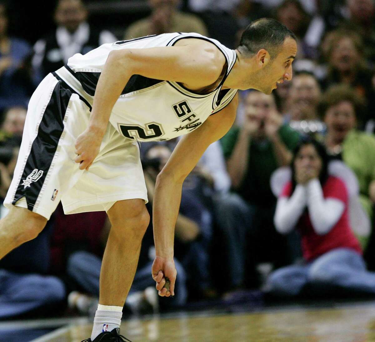 Manu Ginobili picks up a bat to remove it from the court after swatting the animal from the air as it flew around the AT&T Center during the first half of a game against the Sacramento Kings in San Antonio in 2009.