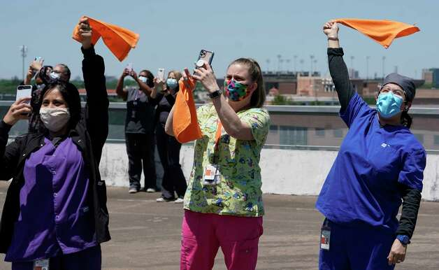 Ashley Armendariz, left, Amanda Trimble, center, and Noelia Flores, right, along with other staff members of UT Physicians Clinics watch the United States Navy Blue Angels flyover from the parking garage roof during a tribute to healthcare workers amid the Covid-19 pandemic Wednesday, May 6, 2020, in Houston. Photo: Melissa Phillip, Staff Photographer / © 2020 Houston Chronicle