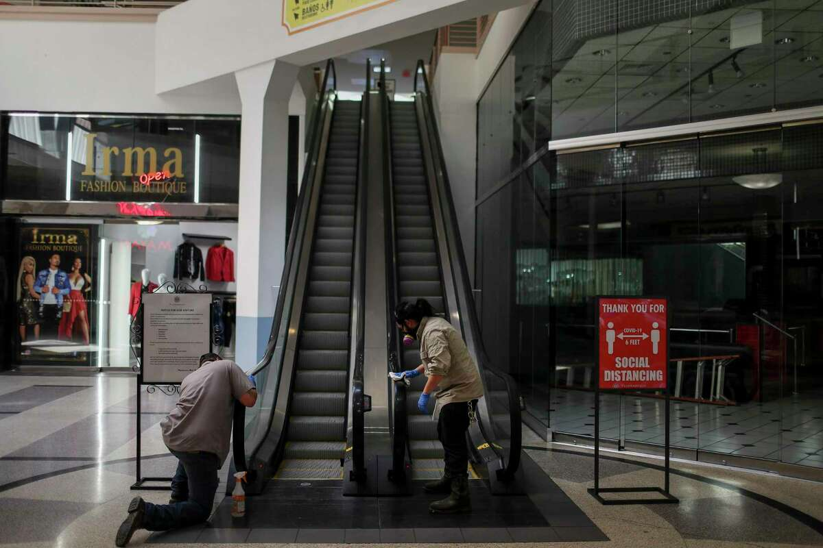 Workers clean an escalator at PlazAmericas mall on Friday. The local economy could lose as many as 83,200 jobs due to a recession caused by the coronavirus.
